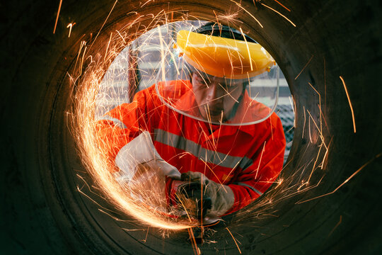 Highly skilled workers wearing industrial uniforms and Welded Iron Mask at Steel use electric wheel grinding on steel structure in the construction industrial factory.industrial safety first concept