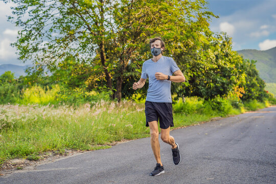 Runner wearing medical mask, Coronavirus pandemic Covid-19. Sport, Active life in quarantine surgical sterilizing face mask protection. Outdoor run on athletics track in Corona Outbreak