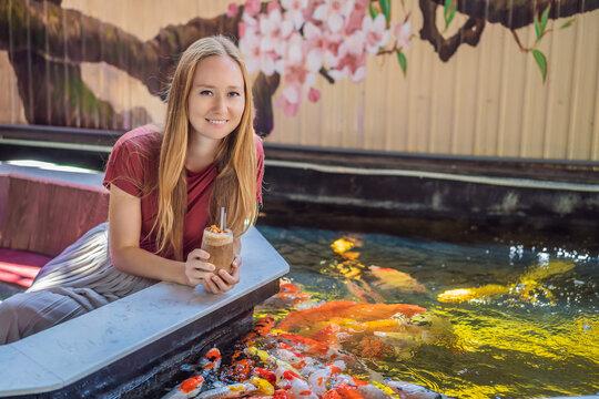 Woman feed koi fish. Beautiful koi fish swimming in the pond