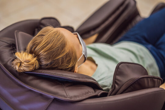 Beautiful young woman wearing a medical mask due to the coronavirus COVID 19 relaxing on the massage chair in airport or in the mall