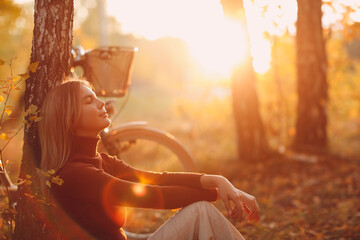 Happy active young woman sitting near vintage bicycle bike in autumn park at sunset. European female enjoying good autumn weather and sunlight.