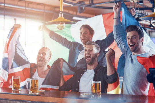 Cheering young men covered in international flags enjoying beer while watching sport game in the pub