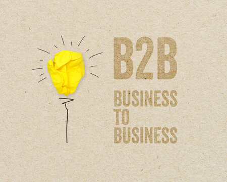 Yellow paper light bulb with B2B - Business to business on brown recycled paper background