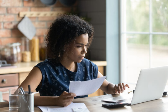 Serious millennial African American woman calculating taxes, budget, costs, checking paper invoice, receipt. Homeowner, tenant using laptop for paying bill, rent, mortgage, insurance fees