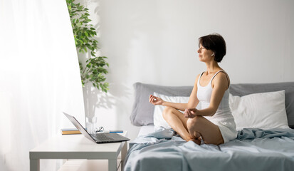 Middle aged caucasian woman in pajamas sitting in lotus position on bed and meditating with closed eyes. Peaceful female using laptop and earphones during morning time at bedroom.