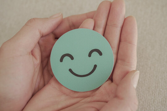 Hand holding green happy smile face paper cut, mental health assessment, child positive wellness, world mental health day concept