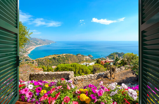 View through an open window with shutters of the beach and coastline of Taormina, Italy, with the sea and the small island Isola Bella in view.