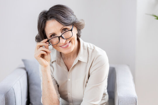 Portrait of a beautiful aged woman with glasses looking at the camera and smiles friendly