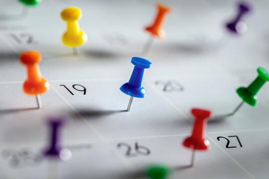 Calendar appointment thumbtacks in various dates on calendar diary