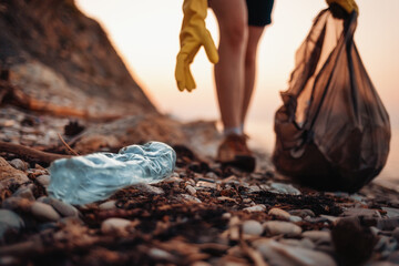 Fototapeta Close up of blue plastic bottle lying on the beach. Close up of volunteer's hands with plastic bag picks up a bottle. The concept of Earth Day and envinmental pollution obraz