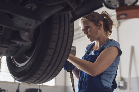 Female mechanic doing a wheel replacement
