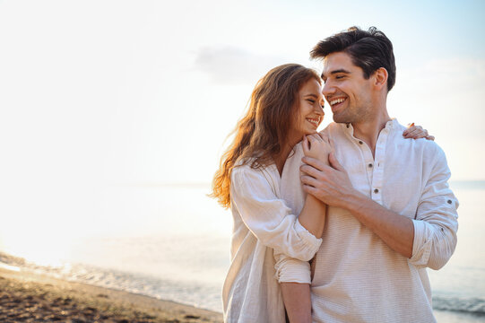 Smiling young couple two friends family man woman 20s in casual clothes hug girlfriend put head on boyfriend shoulder at sunrise over sea sand beach ocean outdoor seaside in summer day sunset evening.