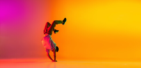 Obraz Flyer with young stylish man, break dancing dancer training in casual clothes isolated over gradient pink yellow background at dance hall in neon light. - fototapety do salonu
