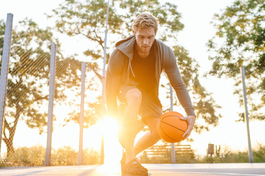 Young cool sunlit european sporty sportsman man 20s wear sports clothes doing handling drills training holding in hand ball play at basketball game playground court Outdoor courtyard sport concept