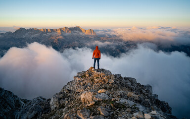 A hiker stands on the ridge watching the valley being flooded by clouds at sunset. Traveling in mountains. Adventure, Art, Travel and Hike concept.