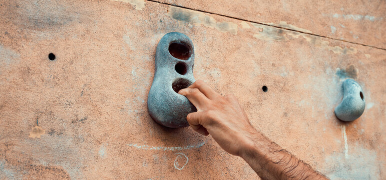 Close-up photo of male hand gripping climbing holds on worn wall outside. Man doing climbing exercise on artificial rock climbing wall at park.