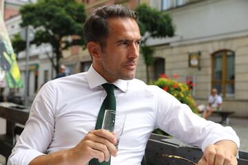 Bardzo przystojny, elegancki mężczyzna w białej koszuli i zielonym krawacie i okularach przeciwsłonecznych.