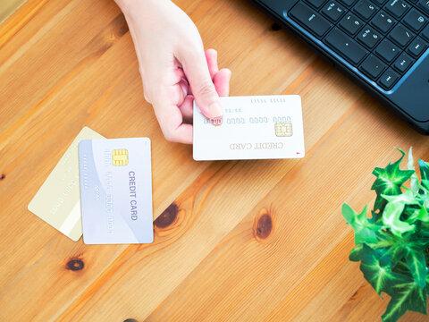 クレジットカードを持ちパソコンを操作する女性の手元