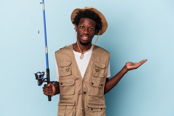 Obraz Young african american fisherman holding a rod isolated on blue background showing a copy space on a palm and holding another hand on waist. - fototapety do salonu