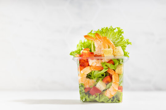 Fresh tropical salad with shrimps, lettuce, red bell pepper, croutons in transparent plastic box on white wood table, marble tile wall.