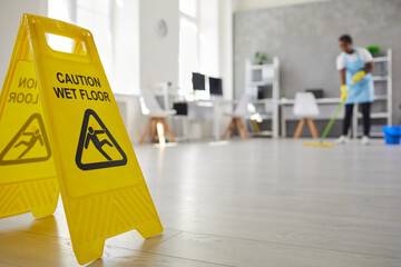 Fototapeta Close up plastic caution sign with figure that slips and falls warning us of wet slippery office floor. Black African American woman caretaker housekeeper cleaning modern room interior in background obraz
