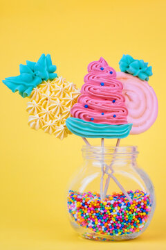 Fruit shaped meringue lollipops on a colorful background