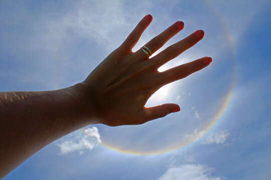 Woman's hand with ring and painted nails covering the sun in a solar halo effect, on a celestial sky.