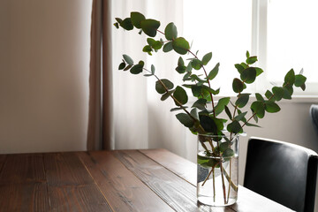 Obraz Vase with eucalyptus branches on table in room - fototapety do salonu