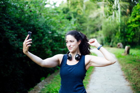 A young caucasian woman wearing with headphones and smartphones taking selfie