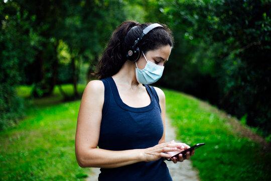 Happy girl with mask in listen music in headphones