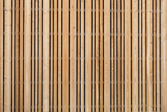 Background modern facade or ceiling made of larch wood strips in the outdoor