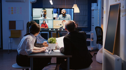 Multi ethnic businesspeople brainstorming company ideas during online videocall conference meeting...