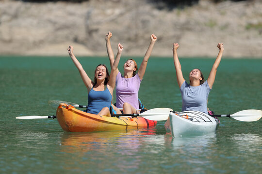 Excited friends celebrating raising arms in kayaks in a lake