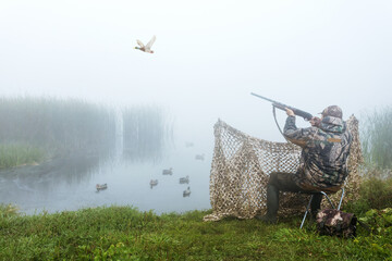 A hunter with a hunting gun and hunting form to hunt in an autumn season on ducks. Hunting period. The man is on the hunt. Hunter man.