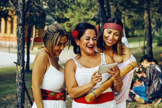 Cheerful Woman Sharing Smartphone With Friends