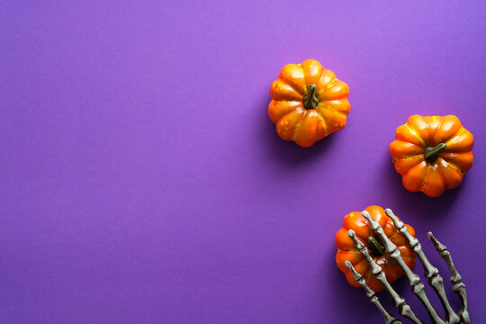 Happy Halloween holiday composition with pumpkins and skeleton hand on violet background. Flat lay, top view, copy space.