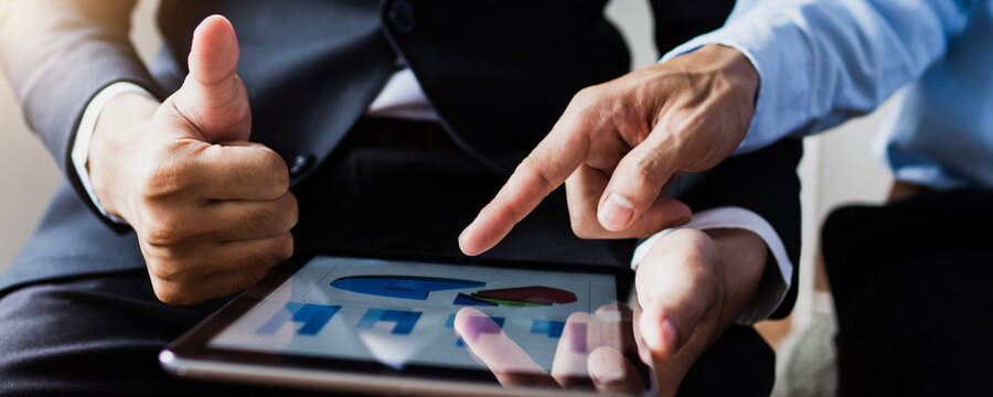 legal and businessman advisor, two business people talking, planning analyze investment and marketing on tablet in office.