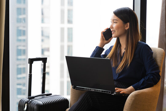 Asian businesswoman using laptop working in hotel room remotely on her business travel