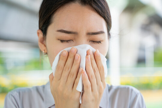 Asian female sneezing in tissue paper blowing running nose. Unhealthy woman suffering illness flu or pollution allergy.