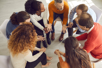Professional therapist meeting with multiracial group therapy patients. Diverse people supporting each other and talking about their issues and ways to solve problems. View from above, high angle shot