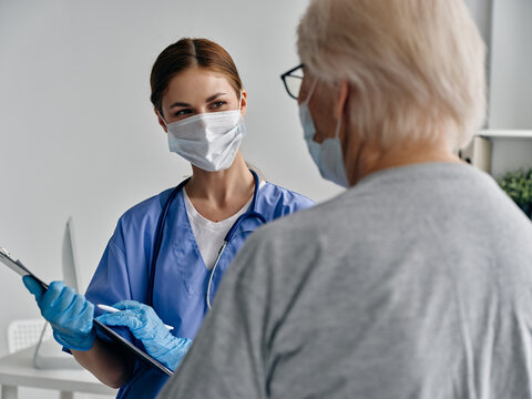 elderly woman patient and nurse with documents medical mask stethoscope vaccine passport