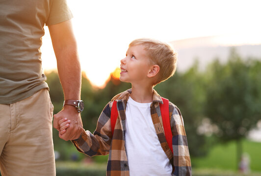 Schoolboy looking at dad with smile while going to first grade in school on sunny autumn day