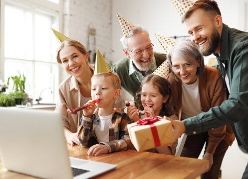 Happy big family celebrating birthday online via video call on laptop while staying at home