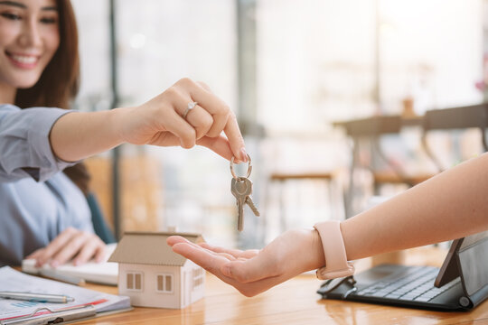 Client taking keys from female real estate agent during meeting after signing rental lease contract or sale purchase agreement. Independent woman purchasing new home, close up view.