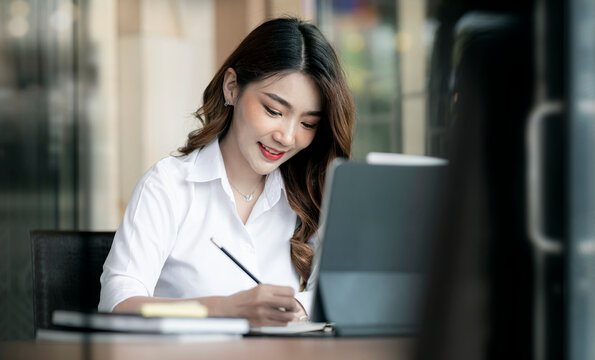 Portrait of young beautiful asian woman working in modern office room with happiness, successful business concept.