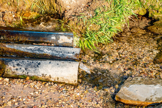 The water flows out of the source with the help of 3 pipes onto the soil. Sunny Summer Day.