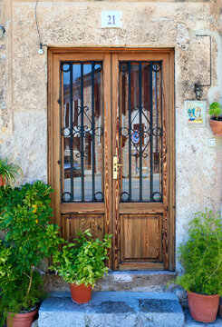 Beautiful elegant wooden door with glass exhibitions and metal grille. Pots with flowers stand on the threshold at home. Old stone house.