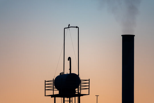 The tall Factory chimney smokes against a beautiful sunset sky.