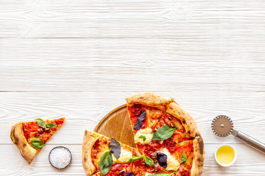 Sliced italian pizza margherita with tomatoes cheese and basil, top view