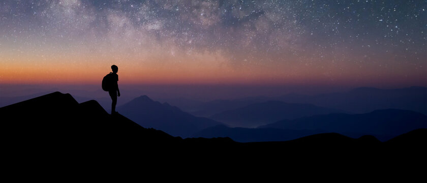 Panorama silhouette of young traveler with backpack standing and watched the star and milky way alone on top of the mountain. He enjoyed traveling and was successful when he reached the summit.